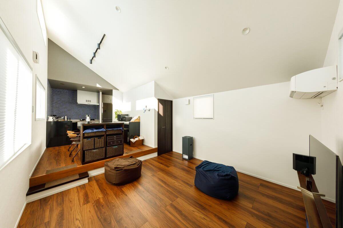 ダイナミックな勾配天井がおもしろい2階LDK。奥のダイニングキッチンをさりげなくセパレートするように、造作の収納棚を設けています。