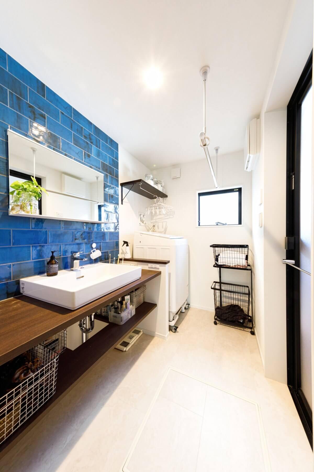爽やかなブルーのタイルで壁一面を飾った洗面室。表面にあえて焼きムラや色ムラがついたタイルで、見れば見るほどに味わい深いです。