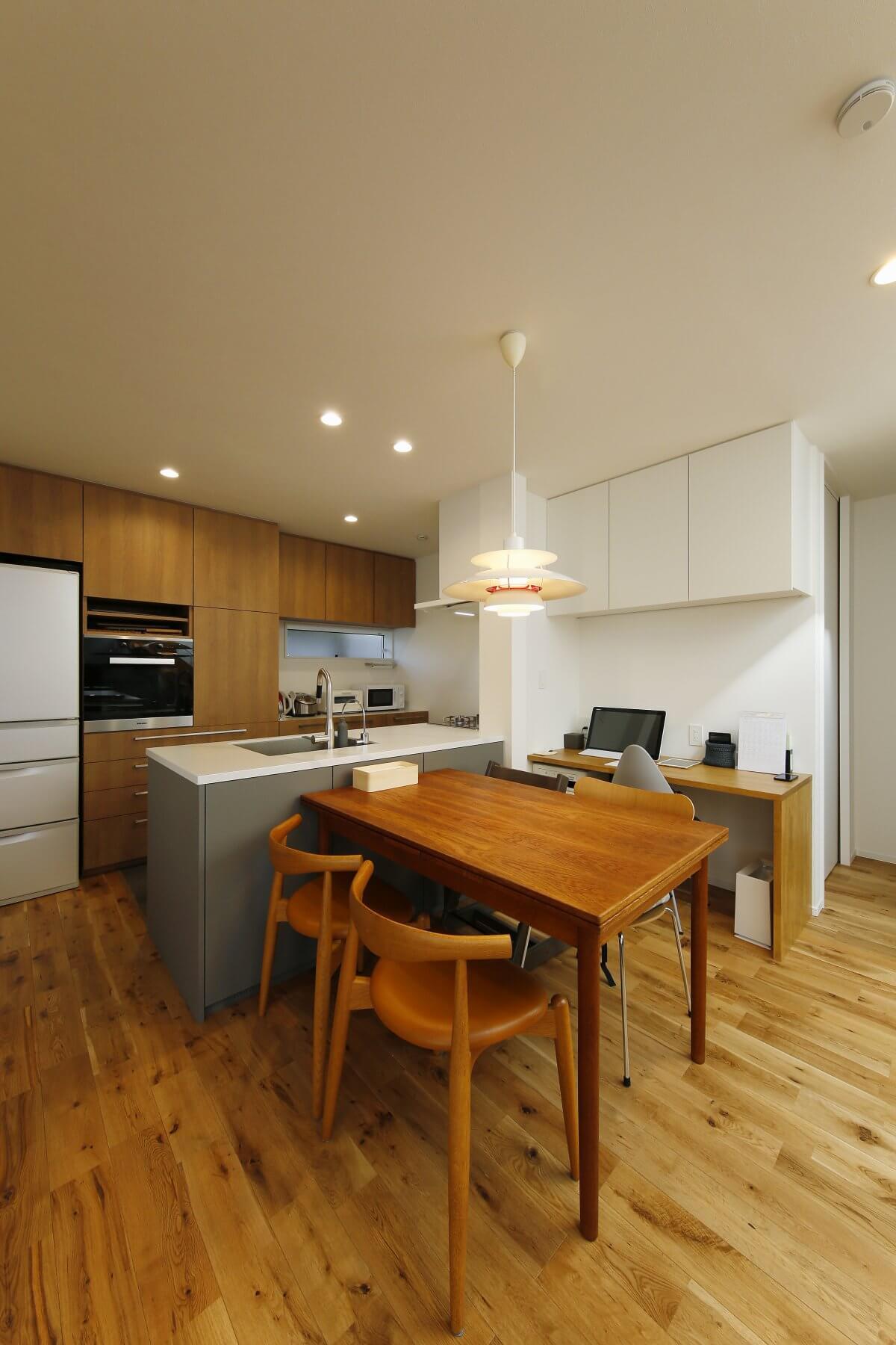 キッチン背面には、ビルトインタイプのオーブンレンジを設けた収納を造作しました。冷蔵庫も使用サイズを採寸しスッキリと収めています。ダイニングテーブルの奥は、テレワークもできる多目的カウンターを造作。