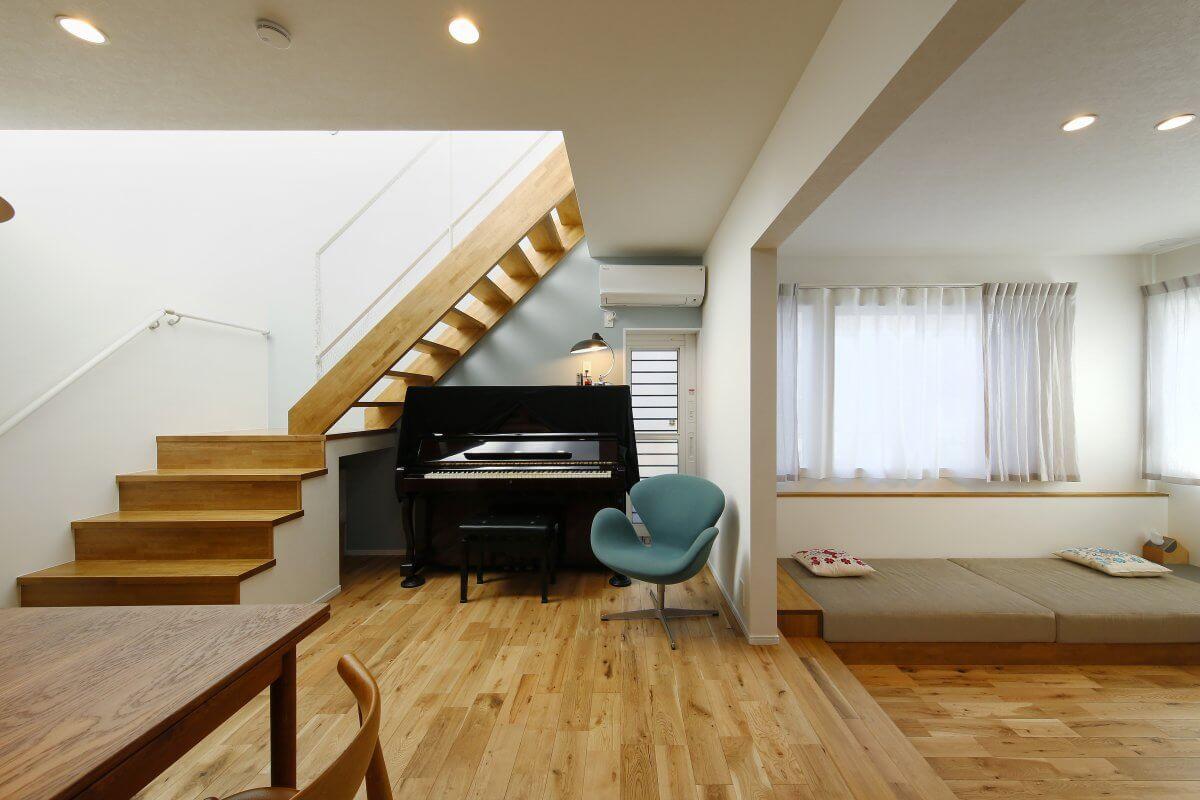 明るい光に包まれるLDK。スキップを下った先がリビングになっており、ソファースペースも造作で造り付けに。階段下のピアノは、勝手口との間にキレイに収まるように、階段の勾配が調整されています。