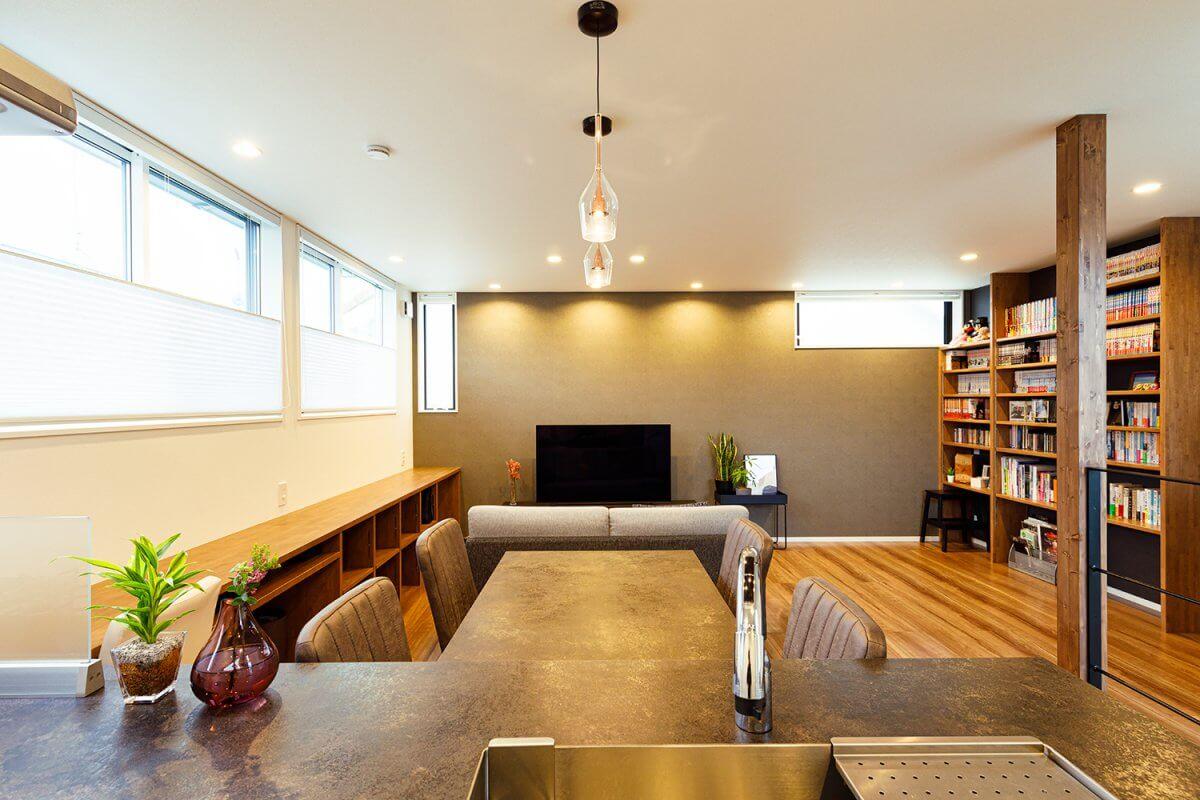 2階LDKのオープンキッチンからの眺め。住宅密集地ながら、周囲の視線を遮りつつ開口部を配置し、常に光にあふれています。壁の一部に壁やダイニングテーブルと同じ系統のアクセントクロスを使い、空間をコーディネートしています。