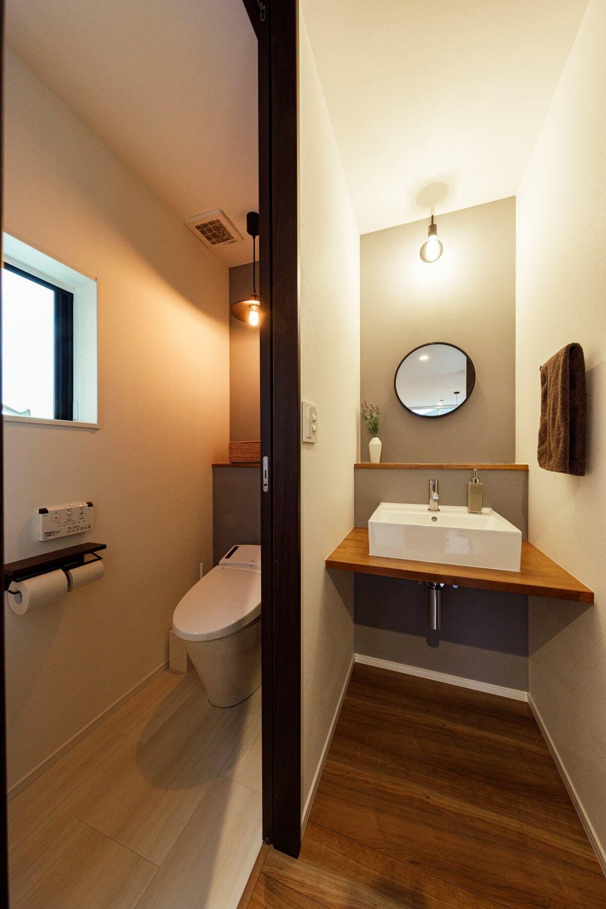 ミニマムサイズで設計したトイレ&手洗いスペース。コンパクトですが、照明や丸い鏡など、細部にわたりデザインにこだわりながら仕上げています。