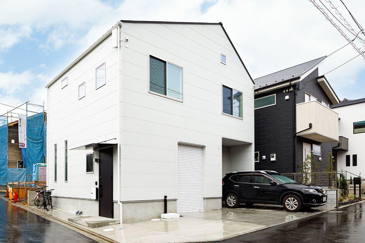 切妻屋根のシンプルなフォルムを追求した外観デザイン。2台分の駐車スペースとバイクガレージを設けています。