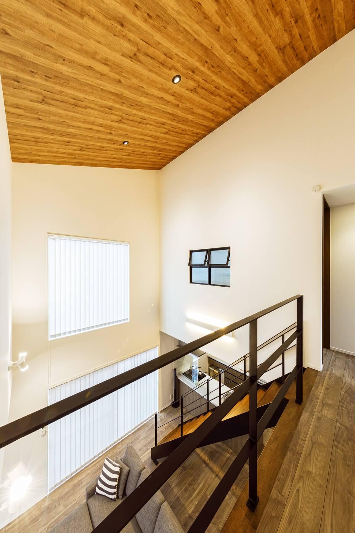 2階の廊下から見た様子。勾配天井には木目調のアクセントクロスを採用。階段の踏み板のトーンとコーディネートしました。