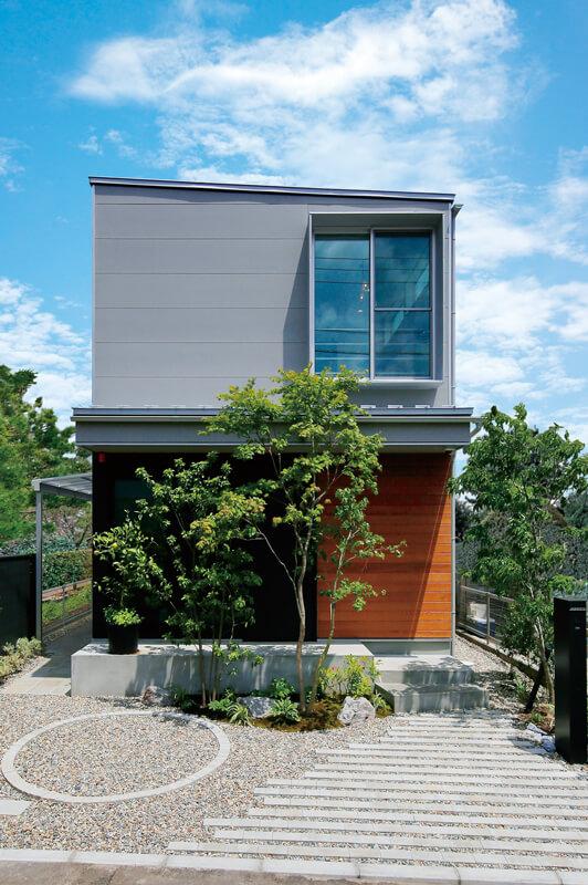 上品なデザインでまとめた外観。2階の窓まわりにはアイアン製の板を型取り、印象的なデザインに仕上げています。外構は緑化率を踏まえながら、こだわりを叶えました。
