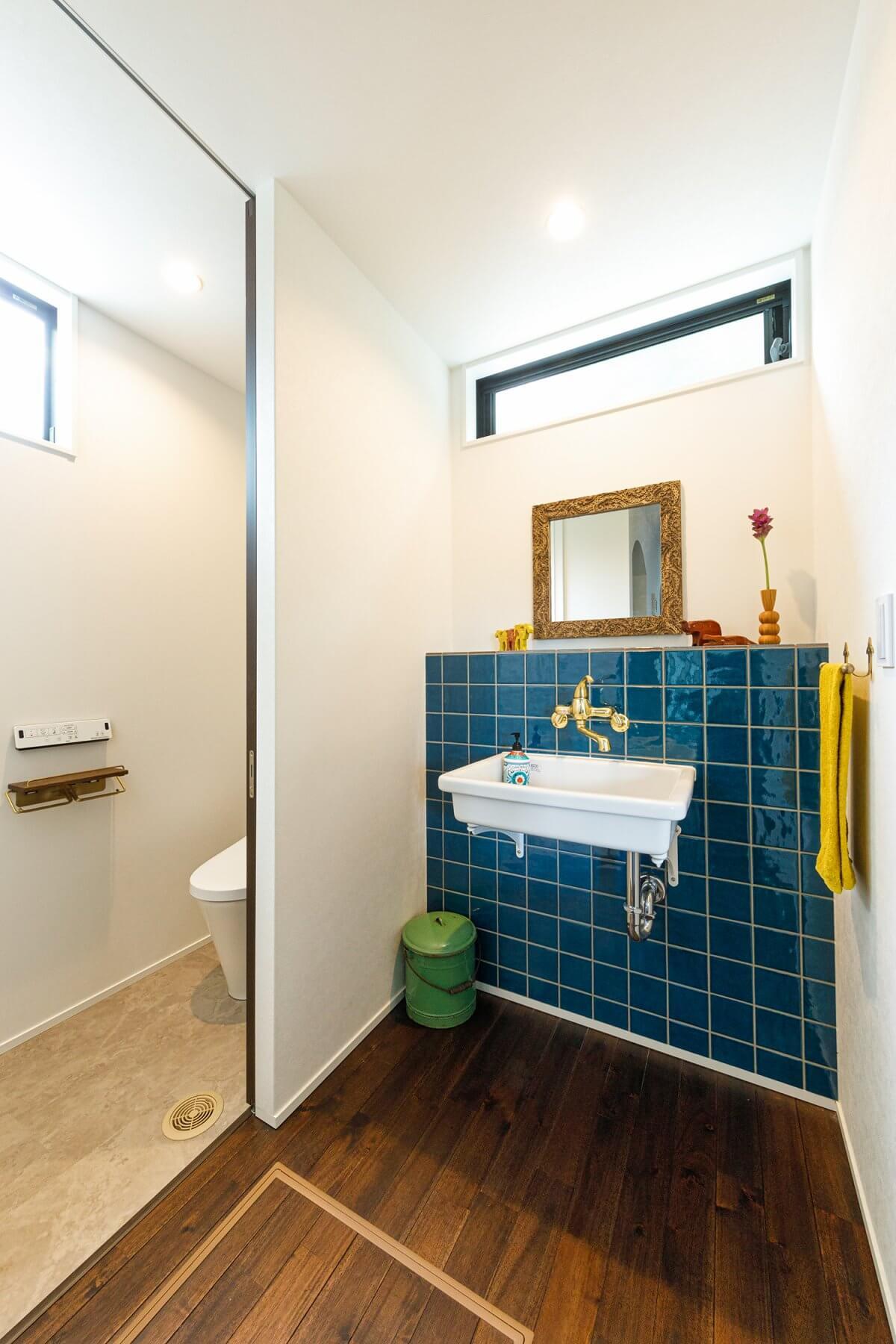 トイレの脇で玄関からも行きやすい場所に、造作の手洗いコーナーを設置。ターコイズブルーのタイルやゴールド色の水栓など、奥様こだわりのデザインがとてもセンス良くコーディネートされています。