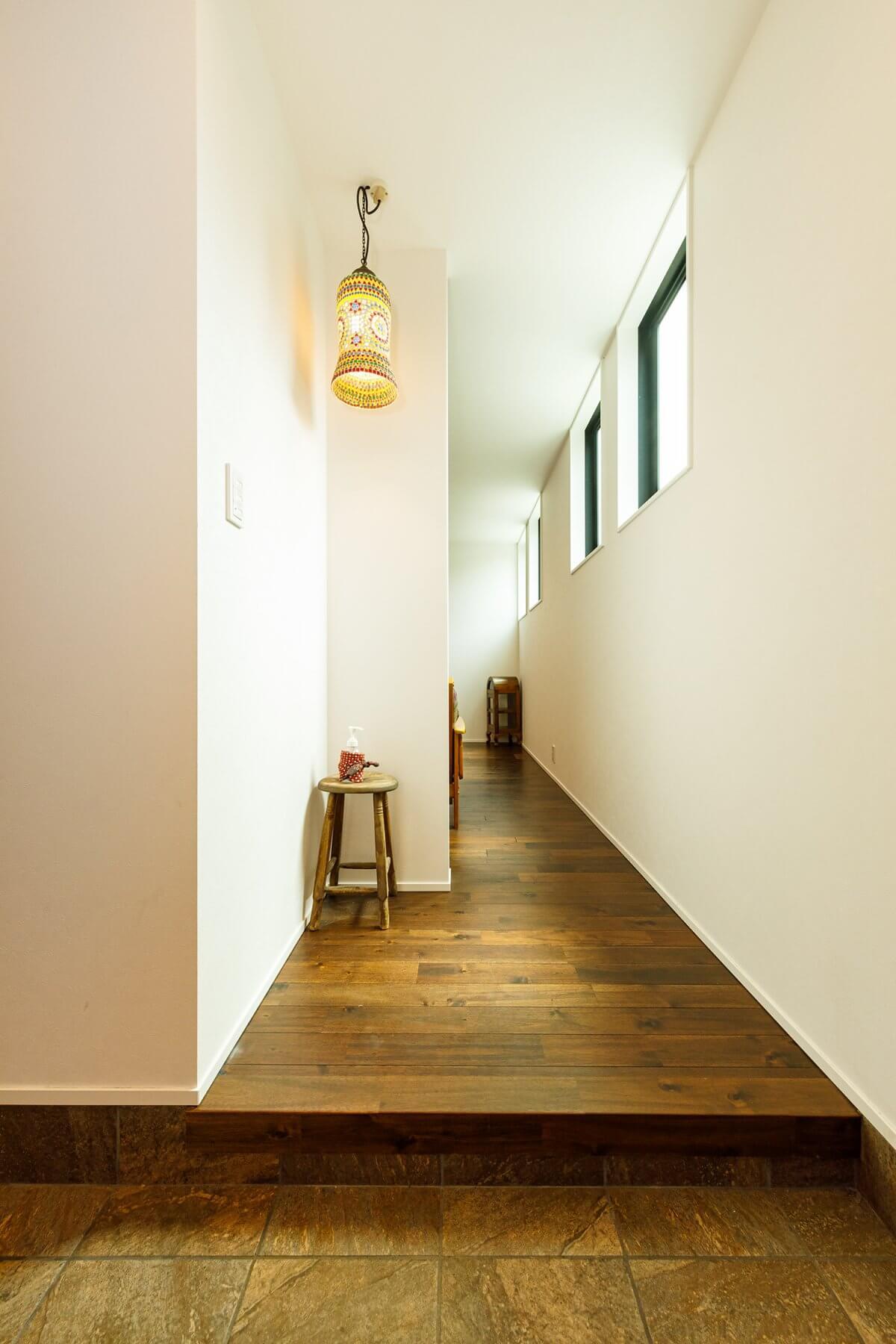 シンプルな玄関には、リビングとの間に建具を設けず、オープンなスタイルに。以前の住まいから大切に使っていたステンドグラスのペンダントライトをぶら下げるスペースを設けて、印象的に空間を演出しました。