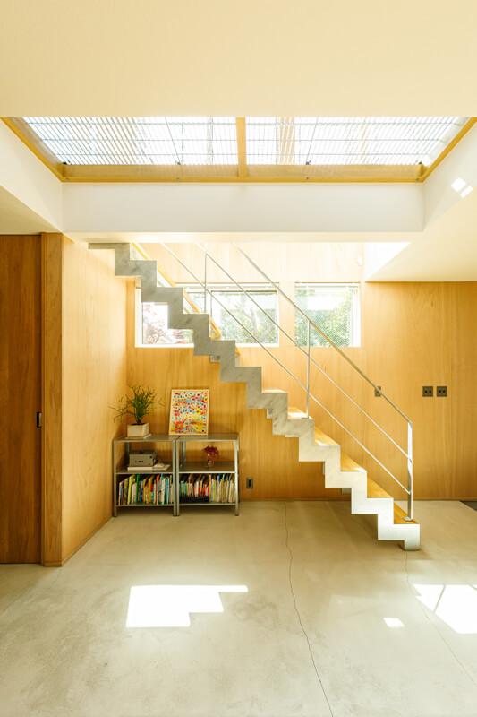 リビング階段と2階のグレーチングを抜けて、やわらかな光が室内に広がります。壁にラワン材をあしらい、落ち着いた空間に仕上げました。