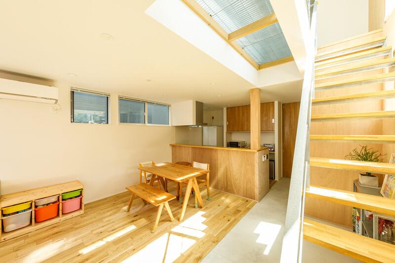 キッチンに立つと玄関まで広く見渡すことができます。階段脇の天井は、メッシュ状のスチールを採用したグレーチング仕上げ。2階の光を1階へと届けています。
