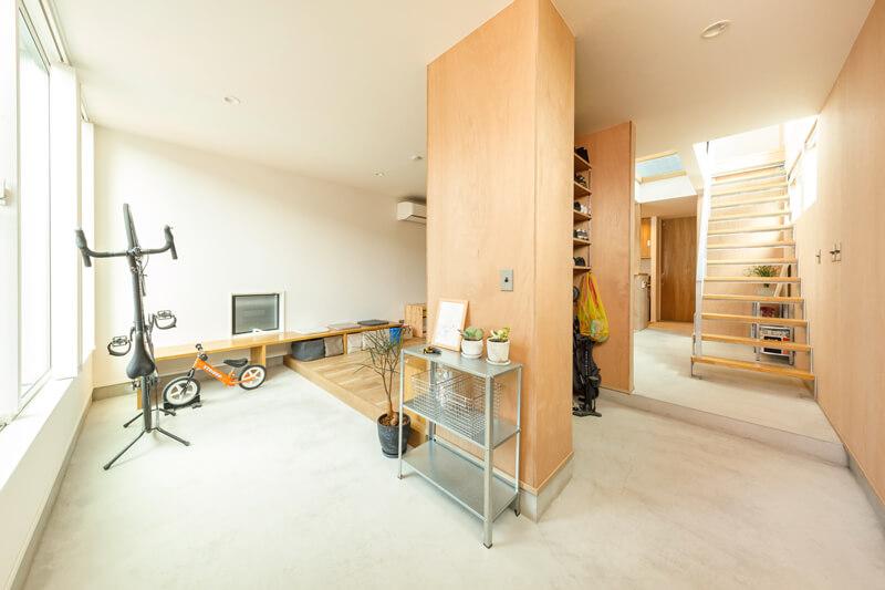 玄関から続くL字の土間空間。屋内にいながら工作室を思わせるアクティブな意匠空間をデザインしました。
