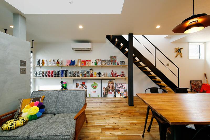 玄関から続く階段下の壁全面をコレクションをディスプレイするギャラリーコーナーに。キッチンからダイニング、そして吹き抜けで住まい全体がゆるやかに、開放的につながっています。
