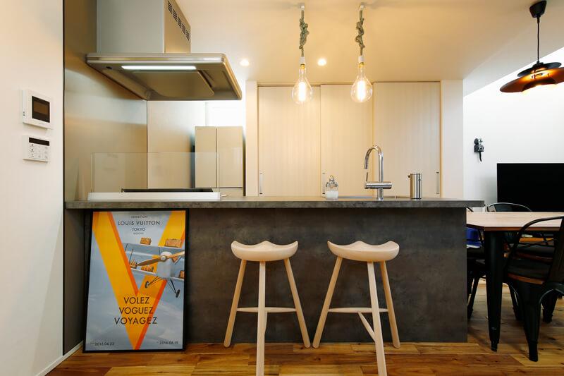 リビングダイニングとは天井の高さを変えて、メリハリをつけたキッチン。ダウンライトに意匠性のあるペンダントライトを組み合わせました。キッチンのワークトップとキャビネットには重厚感のある色彩を合わせ、落ち着きのある空間に。