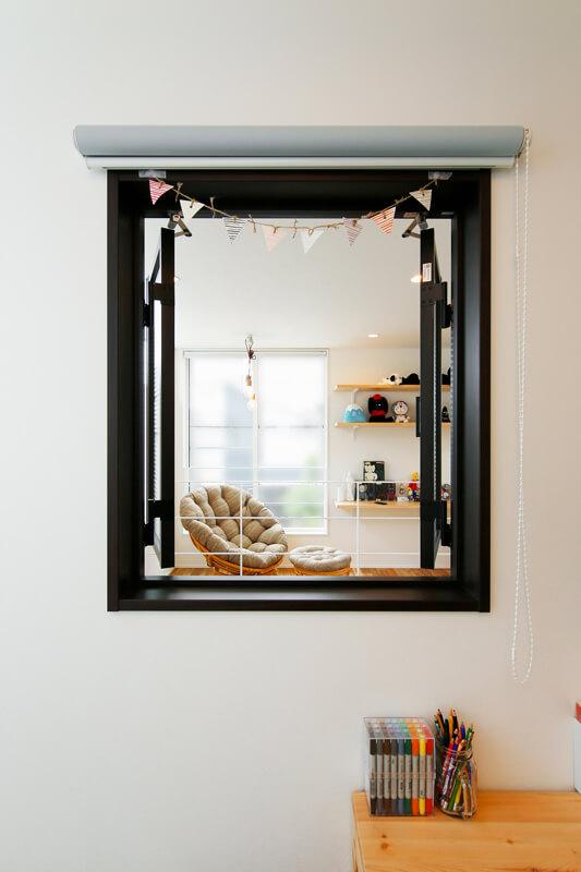 ギャラリースペース手前にある洋室には、吹き抜けに面する形で小窓を設けました。デザインのアクセントだけでなく、住まい全体につながりを意識した設計が施されています。